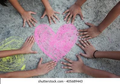 Children hands around the heart