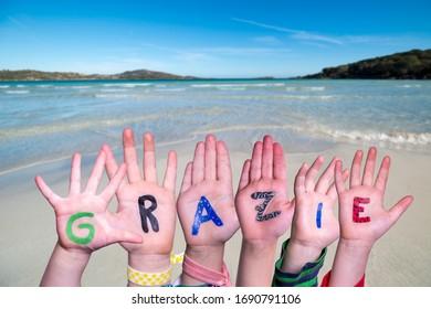 Children Hands Building Word Grazie Means Thank You, Ocean Background