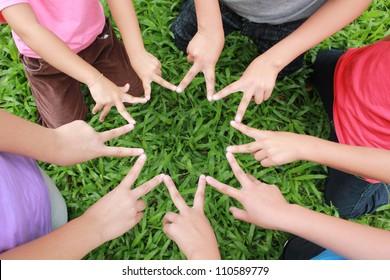 Children hands with green grass background.
