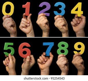 Children hands holding numbers. Black isolated multicolor numbers.