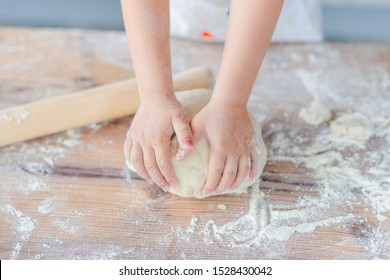 Children hands making the rye dough for backing bread. Kid's hands wheat dough and rolling pin on the table.  Small hands kneading dough.