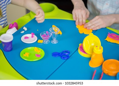 Children hands playing with colorful clay, plasticine in children's room, Creative playing, hands holding hand-made plasticine toy, making plasticine figures