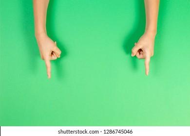 Children hands pointing on pastel green background