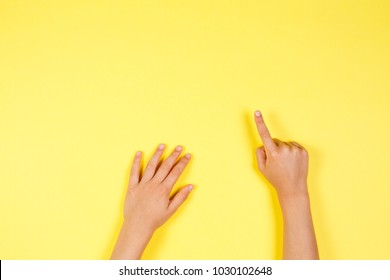 Children hands pointing on yellow background