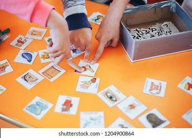 children hands touching white cards of letters numbers and pictures for little kids on the blue table. Time to learn. Education concept. Top view.