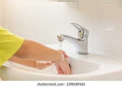 Children hands washed under running water in bathroom sink.