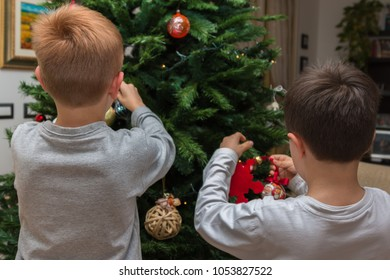 Children Hanging Balls and Decorations on Christmas Tree.