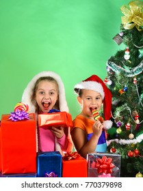 Children with happy faces eat sweets on green background. Kids in Christmas hats with gift boxes open presents. Partying and holiday concept. Girls celebrate Christmas, copy space.