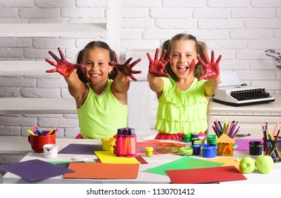 Children happy smiling with colored hands. Imagination, creativity and freedom concept. Girls painters painting with gouache paints on table. Arts and crafts. Kids learning and playing.