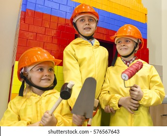 Children in hardhats and yellow overalls with trowel, hammer and roller are ready to do repair indoors. Construction team.