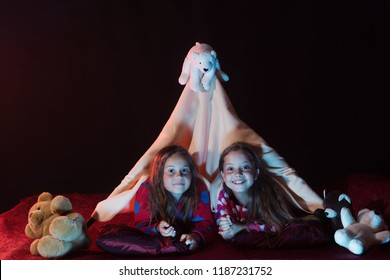 Children have pajama party with teddy bears. Girls with happy faces lie under blanket tent on black background. Childhood and leisure concept. Kids in pajamas covered with blanket lie on pillows