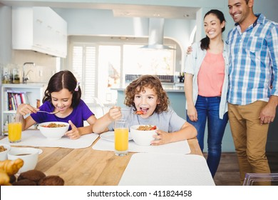 Children having breakfast while happy parents standing by table at home