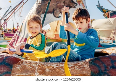 Children having fun at amusement park.  Ride on canoe. Happy childhood concept.