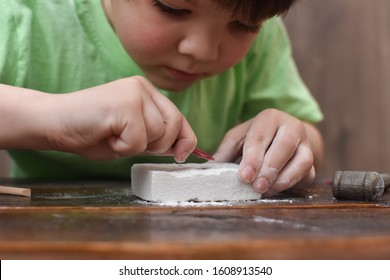 Children having fun with archaeology excavation kit. Boy plays an archaeologist excavated, training for dig fossil