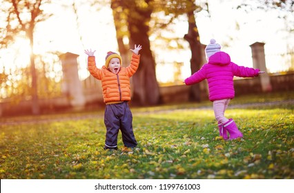 children having fun in beautiful autumnal day. Boy and girl playing outdoors in the park