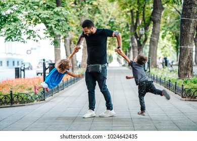Children having fun with dad in the park, daddy twirls kids