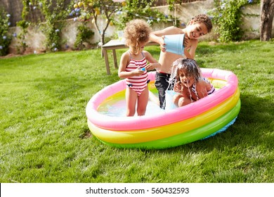 Children Having Fun In Garden Paddling Pool