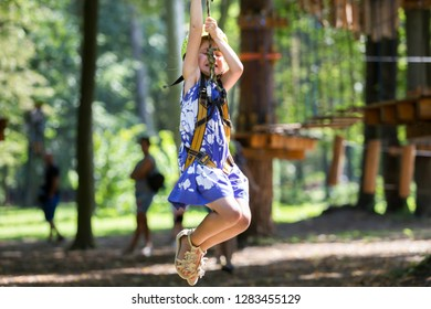 Children having fun on rope way in recreation park. Cute young girl in safety helmet hangs on harness attached with carbine to rope on walking people and green foliage sunny bokeh background.