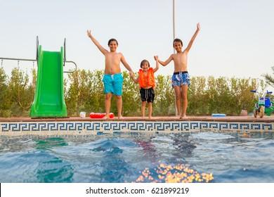 Children having fun on summer swimming pool