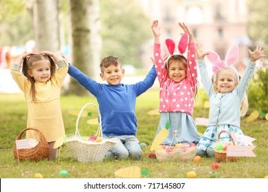 Children having fun in park. Easter egg hunt concept