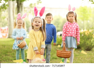 Children having fun in park. Easter egg hunt concept