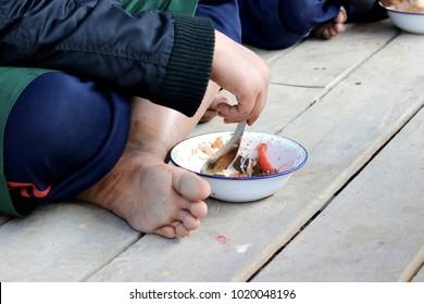Children having lunch in asian school sitting on the floor.