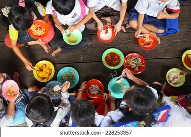 Children having lunch in asian school sitting on the floor