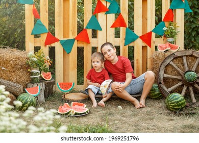 Children having picnic outdoors in summer park. Funny kids eating watermelon outdoors in the garden. Happy boys eating watermelon. Healthy eating, snack for children. Childhood. Summer time. Friends