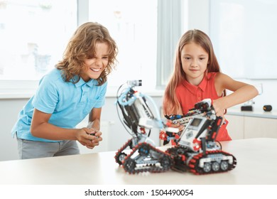 Children having robotics class playing with robots holding controllers having fight laughing cheerful