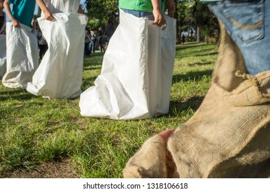 Children having a sack race in the park. Classic games concept. Motion blurred