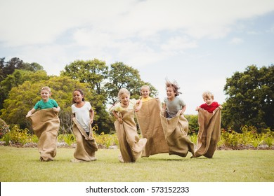 Children having a sack race in park on a sunny day