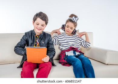 Children with headphones and digital tablet sitting on sofa on gray
