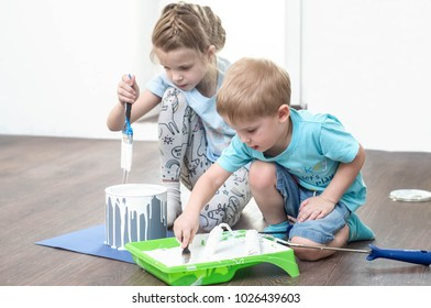 Children help in repairs: a boy and a girl dunk brushes and a roller into white paint for painting walls