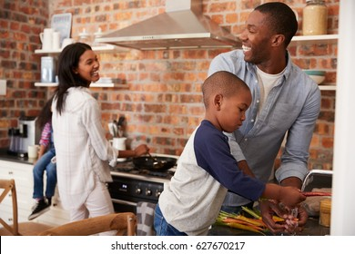 Children Helping Parents To Prepare Meal In Kitchen