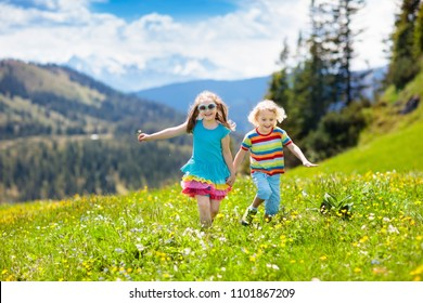 Children hiking in Alps mountains. Kids run at snow covered mountain in Austria. Spring family vacation. Little boy and girl on hike trail in blooming alpine meadow. Outdoor fun and healthy activity.