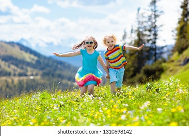 Children hiking in Alps mountains. Kids run at snow covered mountain in Austria. Spring family vacation. Little boy and girl on hike trail in blooming alpine meadow. Outdoor fun and healthy activity