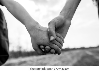 Children hold hands together on a walk on a summer day. Black and white photo.