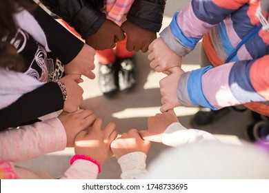 Children holding hands from different culture and race with different skin tones and showing unity top angle shot from children's hands holding each others fingers with love