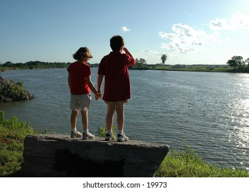 Children holding hands looking at a lake.