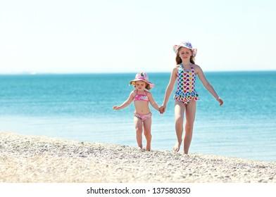 Children holding hands running on beach