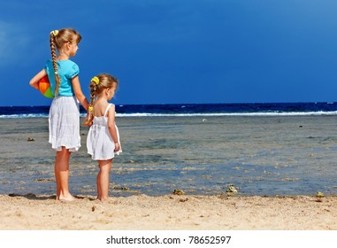 Children holding hands walking on the beach. Rear view.