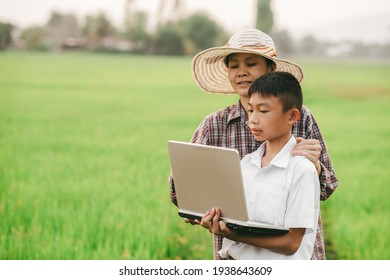 Children holding laptop and mother on rice field background