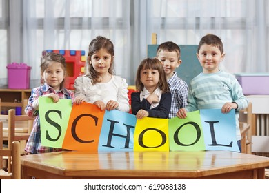 Children holding SCHOOL sign in the classroom.