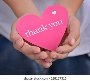 Children holding or showing card with thank you text