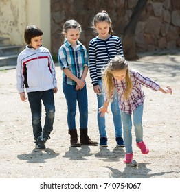 Children hopscotching and laughing in playground outdoors