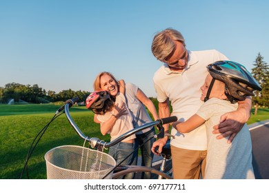 children hugging happy grandparents while standing near bicycle
