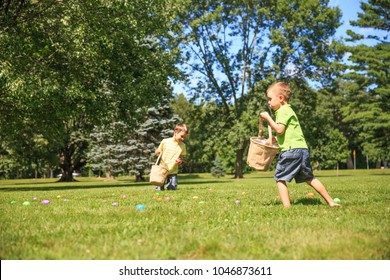 children hunt for Easter eggs. happy kids pick up colorful eggs. the concept of Easter Egg Hunt. copy space for your text