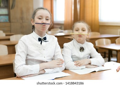 Children indulge in school in the classroom make face mimicry. Two schoolgirls pinch a pencil with their lips to the nose make a funny facial expression.