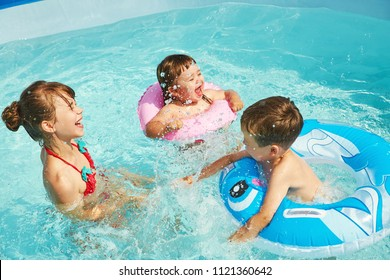 children in inflatable swimming circle playing in swimming pool
