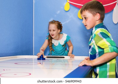Children intently and enthusiastically play table hockey.